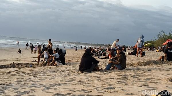 Ramainya kunjungan wisatawan di Pantai Kuta juga dimanfaatkan oleh para pedagang untuk mengais rezeki. Sejumlah pedagang makanan ringan dan minuman juga nampak berkeliling menawarkan dagangannya. (Sui Suadnyana/detikTravel)