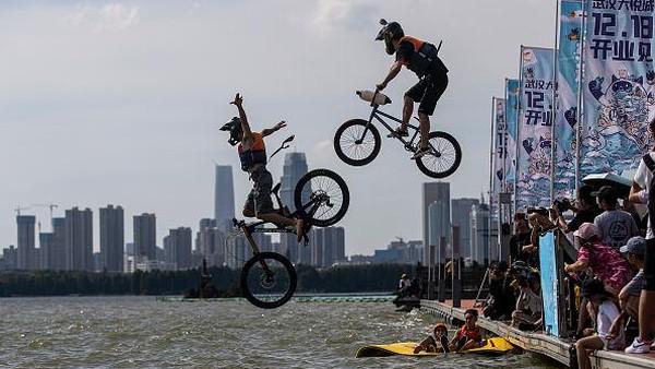 Menariknya, di festival tersebut warga dibolehkan melompat ke danau menggunakan sepeda hingga skuter.