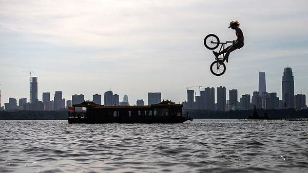 Seorang pesepeda melompati danau saat ambil bagian dalam festival lompat air yang digelar di Wuhan, Provinsi Hubei, China, Sabtu (25/9/2021).