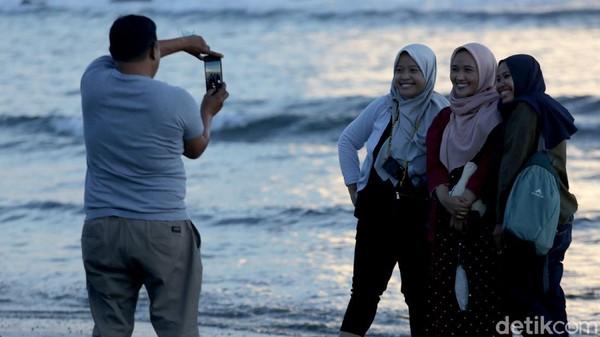 Sejumlah wisatawan berfoto dengan latar laut saat matahari terbenam di pantai Sebalang, Lampung.