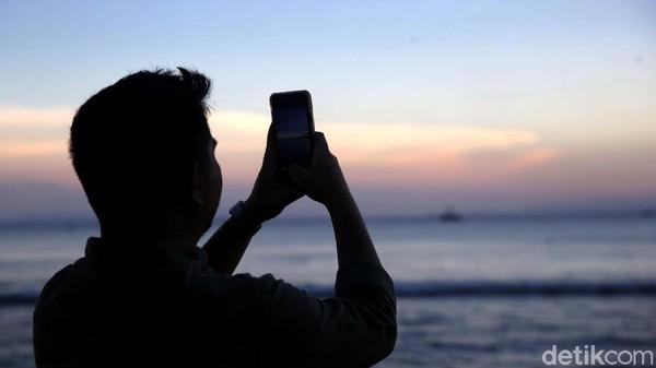 Seorang wisatawan memotret pemandangan matahari terbenam di Pantai Sebalang, Lampung.
