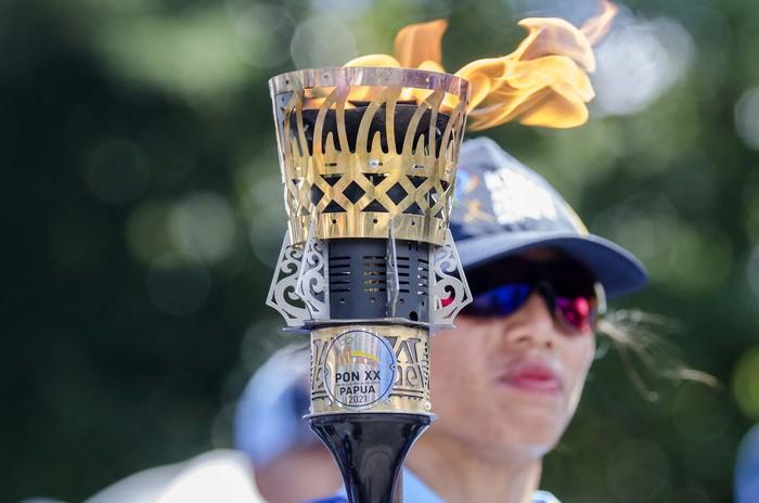 Sejumlah warga menyambut atlet dan mantan atlet asal Papua saat membawa api obor Kirab Api PON XX Papua di Alun-alun Kuala Kencana, Kabupaten Mimika, Papua, Selasa (28/9/2021). Api PON XX Papua diarak di beberapa wilayah yakni Sorong, Biak, Timika, Wamena, Merauke, Kabupaten Jayapura, Kota Jayapura dan berakhir di Stadion Lukas Enembe untuk upacara penyalaan Kaldron pada Pembukaan PON XX Papua. ANTARA FOTO/Novrian Arbi/YU