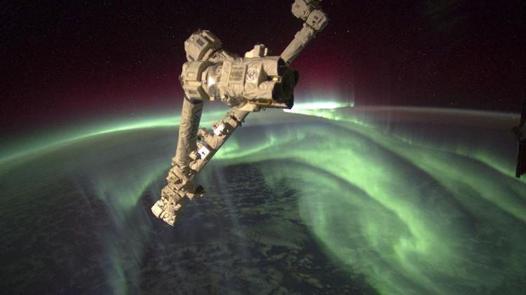 Penampakan spektakuler aurora seakan menyelimuti Bumi, dari titik 240 kilometer di atas sana memperlihatkan cahaya hijau aurora tinggi di atmosfer sementara di kejauhan, ada sinar kemerahan. Sedangkan di bawahnya adalah area awan-awan yang berarak di atas lautan.
