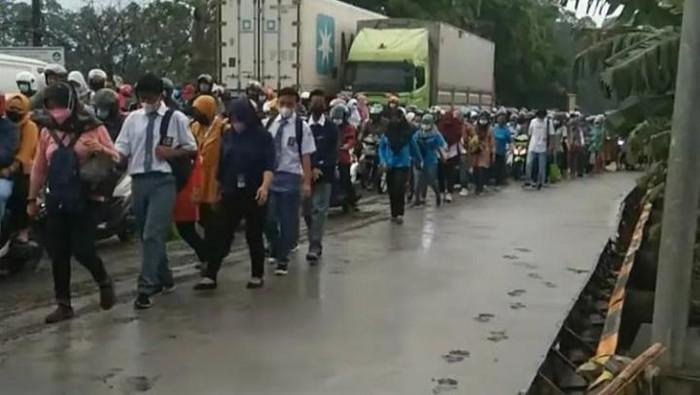 Warga melintas di jalan yang baru dicor di Kabupaten Tangerang. Pengecoran jalan itu belum kering hingga menimbulkan bekas sepatu dan roda (dok.istimewa)