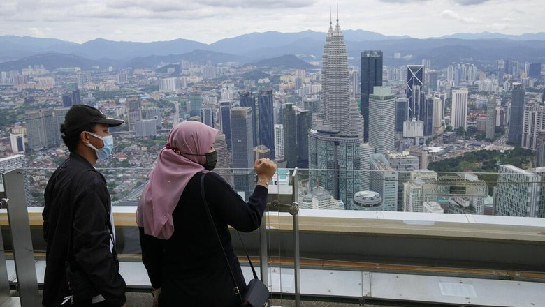 Tourists wearing face masks take photos on an observation deck at the Kuala Lumpur Tower in Kuala Lumpur, Malaysia, Friday, Oct. 1, 2021. Public recreational parks were allowed to reopen for leisure activities under Malaysias National Recovery Plan, amid the coronavirus disease (COVID-19) pandemic restrictions. (AP Photo/Vincent Thian)