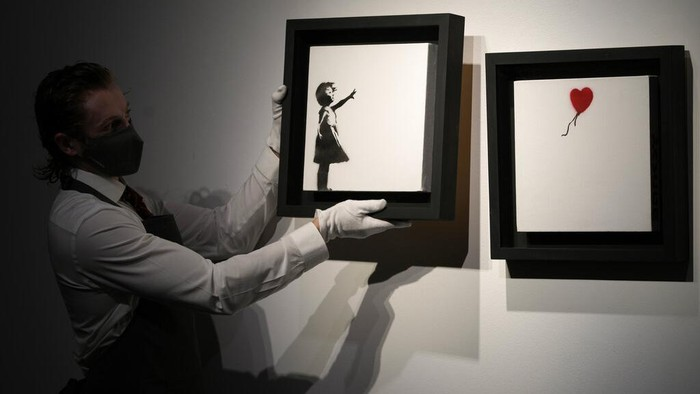 Members of staff hold up an artwork by British graffiti artist Banksy entitled 'Girl and Ballon' (two parts), during a pre-auction press viewing at Christie's auction house in London, Friday, Oct. 1, 2021. The diptych is expected to sell for 2,500,000 million pounds sterling (US, $3.5-4.8 million, euros 3-4.1 million). (AP Photo/Alastair Grant)