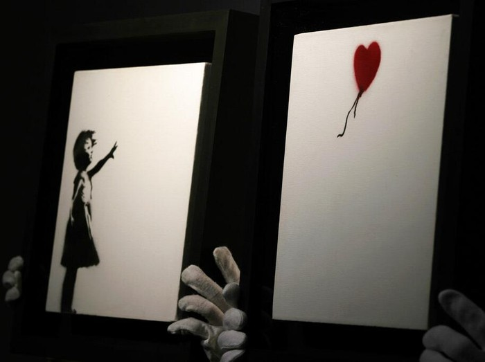 Members of staff hold up an artwork by British graffiti artist Banksy entitled Girl and Ballon (two parts), during a pre-auction press viewing at Christies auction house in London, Friday, Oct. 1, 2021. The diptych is expected to sell for 2,500,000 million pounds sterling (US, $3.5-4.8 million, euros 3-4.1 million). (AP Photo/Alastair Grant)