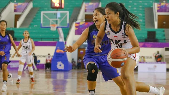 Duel Yuliana asal DKI Jakarta (kanan) dengan Natalia Kumaat asal Papua pada laga penyisihan grup basket putri di GOR Sport Centre, Timika, Kabupaten Mimika, Papua, Senin (4/10/2021)  (Foto: PB PON XX PAPUA 2021/Peksi Cahyo)