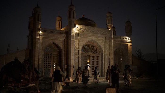 Taliban fighters walk at the entrance of the Eidgah Mosque after an explosion in Kabul, Afghanistan, Sunday, Oct. 3, 2021. A bomb exploded in the entrance of the mosque in the Afghan capital on Sunday leaving a