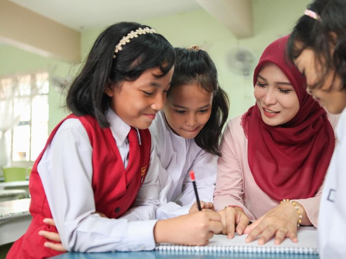 A Malay Muslim female teacher teaching a group of students in a classroom in Malaysia.
