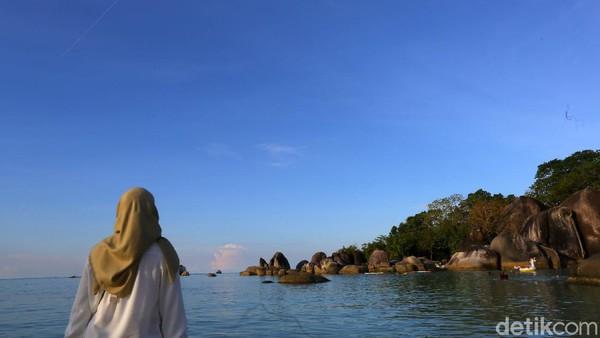Seorang pengunjung menikmati keindahan Pantai Tanjung Tinggi yang identik dengan gugusan bebatuan besar alaminya.