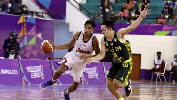 Pebasket DKI Jakarta, Yesaya Alessandro Saudale dikawal ketat oleh pebasket Jawa Timur, Andreas Marcellino Bonfillio pada pertandingan semifinal Bola Basket 5x5 Putra PON XX Papua di GOR Basket Mimika Sport Complex, Kamis (7/10/2021).