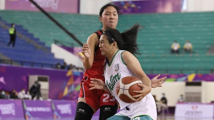 Pebasket DKI Jakarta, Shopia Rebecca (merah) berusaha menahan pergerakan pemain Jawa Timur, Christine Aldora Tjundawan pada pertandingan Semifinal Bola Basket 5x5 Putri PON XX Papua di GOR Basket Mimika Sport Complex, Kamis (7/10/2021). (Foto : PB PON XX Papua / Ady Sesotya)