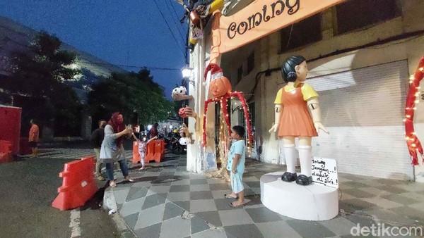 Boneka berambut pendek, rambutnya diikat dua bagian bawah dan memakai baju oranye ini terlihat menyeramkan dalam serial Squid Game. Rupanya, bagi yang sudah menonton juga merasakannya saat boneka Squid Game ada di Jalan Tunjungan.