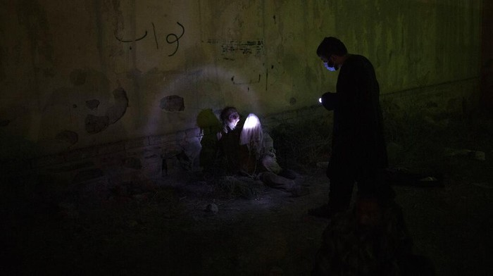 A Taliban fighter uses a flashlight to wake up a drug user detained during a police raid in Kabul, Afghanistan, Friday, Oct. 1, 2021. Now the uncontested rulers of Afghanistan, the Taliban have set their sights on stamping out the scourge of narcotics addiction, even if by force. (AP Photo/Felipe Dana)