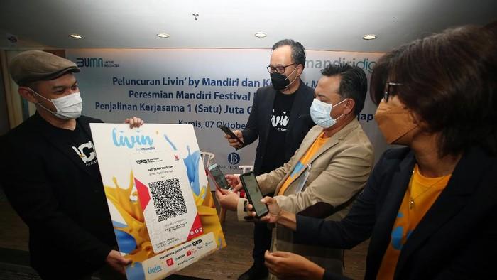 Regional CEO Bank Mandiri Jakarta 1 Teuku Ali Usman  berbincang dengan Vice President Yayasan Aksi Cepat Tanggap (ACT) Aulia Ikhsan seusai penandatanganan  penyediaan 1 juta QRIS (Quick Response Indonesian Standar) untuk berdonasi melalui ACT sebagai bagian dari peringatan HUT Bank Mandiri ke-23, di Tangerang Selatan, Banten, Kamis (7/10/2021).  Sebagai wujud transformasi menjadi modern digital bank, Bank Mandiri meluncurkan super app: Livin' by mandiri yang dapat digunakan untuk transaksi  digital pada Mandiri Festival Belanja, yang diikuti 1000 merchant lebih di Banten, dan menghadirkan super app: Kopra by mandiri untuk mendukung pengelolaan keuangan pelaku usaha, serta bermitra dengan 1.053 agen Mandiri di kawasan Banten, agar masyarakat dapat membuka rekening ataupun transaksi finansial tanpa perlu datang ke kantor cabang.