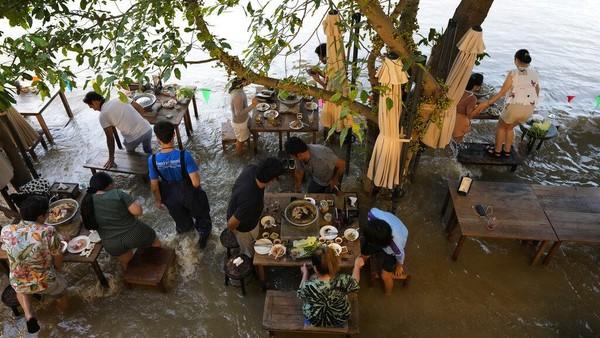 Diketahui, restoran yang berada di pinggir sungai itu tengah jadi destinasi populer warga di Negeri Seribu Pagoda. Bukan tanpa alasan, mereka datang ke sana untuk merasakan sendiri makan di tengah banjir.
