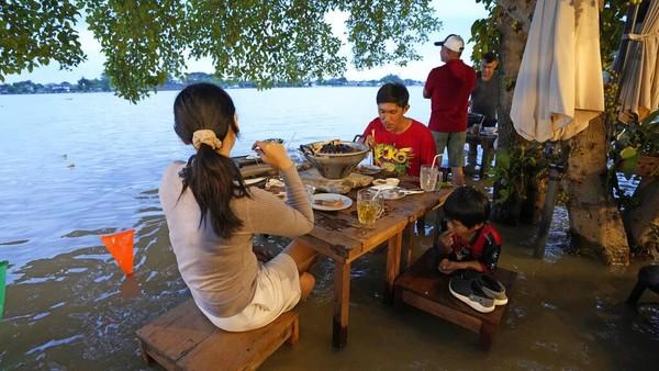 Bila air sungai tengah meluap biasanya sejumlah restoran di pinggir sungai pun sepi pengunjung. Namun kondisi itu berbeda dengan restoran ini. Pengunjung justru berdatangan untuk makan di tempat saat restoran tersebut tengah direndam banjir.
