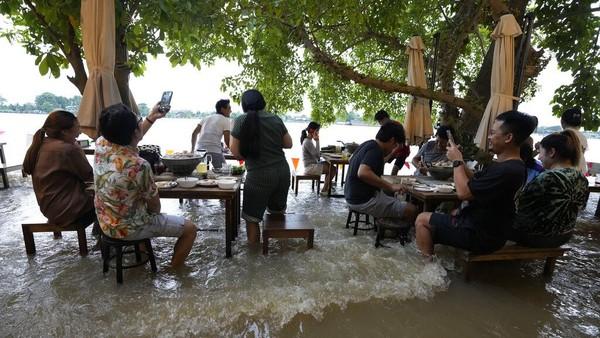 Sejumlah pengunjung tengah menyantap makanan di tengah banjir yang merendam sebuah restoran di kawasan Nonthaburi, dekat Bangkok, Thailand.