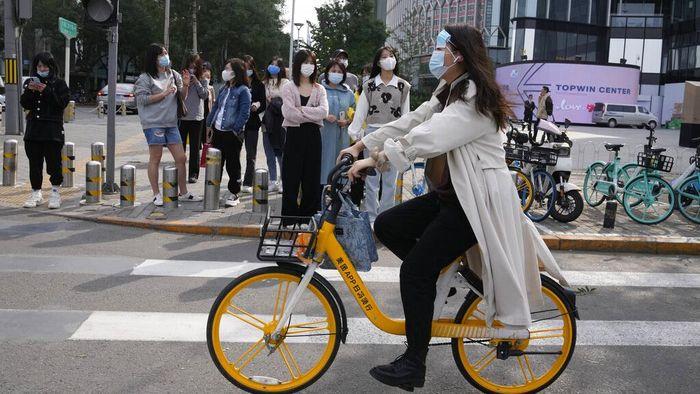 Pemandangan tak biasa terlihat di jalanan Beijing, China. Seorang warga mengenakan masker sampai dua sekaligus saat beraktivitas di luar rumah. Ini fotonya.
