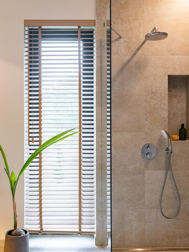 Shower separated by a glass wall from the window.