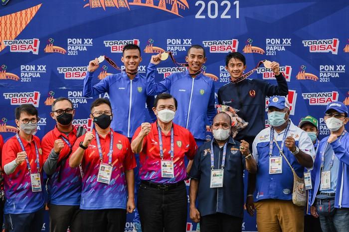 Menko Kemaritiman sekaligus Ketua Umum PB PASI Luhut Binsar Pandjaitan (tengah-bawah) bersama Menteri Kesehatan Budi G Sadikin (ketiga kiri) dan pejabat terkait berfoto bersama atlet peraih medali yaitu pelari Jawa Barat Agus Prayogo (tengah) bersama pelari Jawa Barat Pandu Sukarya (kiri) dan pelari Bangka Belitung Robi Sianturi pemenang pada nomor lari 5000 meter PON XX Papua di Stadion Atletik, Mimika Sport Complex, Selasa (5/10/2021). PB PON XX Papua / Rommy Pujianto