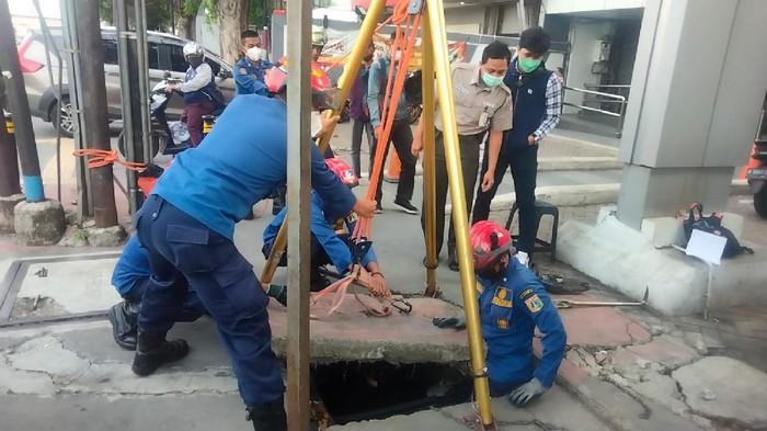 Petugas Damkar mengevakuasi kartu ATM yang jatuh ke Gorong-gorong Jakarta Timur.