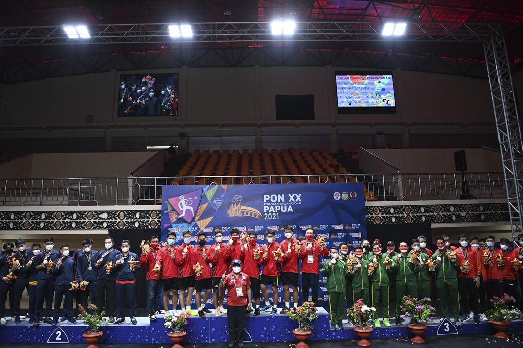Tim bulu tangkis putra DKI Jakarta (tengah), tim bulu tangkis putra Jawa Barat (kiri), tim bulu tangkis putra Jawa Tengah dan Jawa Timur (kanan) berfoto bersama usai Upacara Penghormatan Pemenang final beregu putra PON Papua di GOR Waringin Kotaraja, Kota Jayapura, Papua, Sabtu (9/10/2021). Tim bulu tangkis DKI Jakarta meraih medali emas, disusul tim Jawa Barat meraih medali perak dan tim Jawa Tengah dan Jawa Timur meraih medali perunggu. ANTARA FOTO/Nova Wahyudi/wsj.