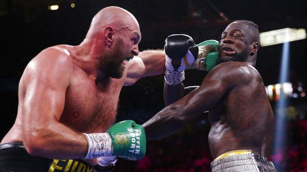 Tyson Fury, of England, lands a left to Deontay Wilder in a heavyweight championship boxing match Saturday, Oct. 9, 2021, in Las Vegas. (AP Photo/Chase Stevens)