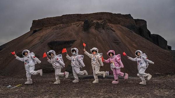 Sejumlah orang dengan kostum astronot menikmati liburan di area kompleks gunung berapi China di Ulan Hada Volcano Geopark.