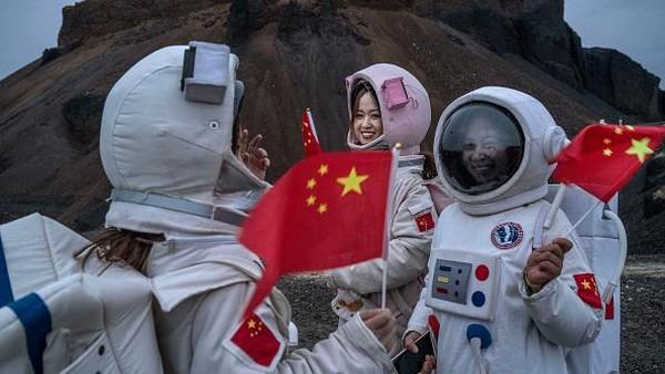 Pengunjung yang mengenakan kostum astronaut ini mengunjungi Volcano No. 6 dari kawasan Ulan Hada Volcano Geopark dekat Ulanqab.