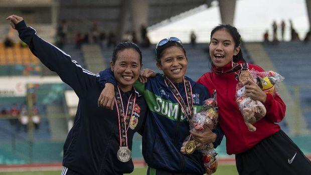 Pelari Sumatera Selatan Sri Mayasari (tengah), pelari Bengkulu Hasruni (kiri), dan pelari DKI Jakarta Jeany Nuraini (kanan) berpose usai pengalungan medali lari 200 meter putri PON Papua di Stadion Atletik Mimika Sport Center, Kabupaten Mimika, Papua, Senin (11/10/2021). Hasruni meraih medali perak, sementara pelari Sumatera Selatan Sri Mayasari meraih medali emas dan pelari DKI Jakarta Jeany Nuraini meraih medali perunggu. ANTARA FOTO/Aditya Pradana Putra/tom.