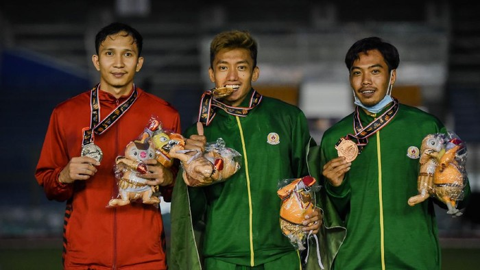 Atlet lompat tinggi galah Jawa Timur Teuku Tegar Abadi (tengah) DKI Jakarta  (kiri) dan Jawa Timur Dedi Irawan menunjukkan medali yang diterimanya seusai mengikuti nomor lompat tinggi galah putra PON XX Papua di Stadion ATletik, Mimika Sport Complex, Senin (11/10/2021). PB PON XX Papua / Rommy Pujianto
