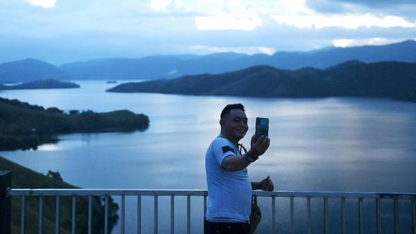 Seorang pengunjung berfoto dengan latar panorama alam di kawasan Bukit Teletubbies Kampung Doyo Lama, Distrik Waibhu, Kabupaten Jayapura, Papua, Senin (11/10/2021).