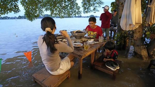 Walau air menggenang, hal ini tak menyurutkan langkat wisatawan untuk datang. Justru, mereka terlihat begitu menikmati pengalaman unik ini.(Sakchai Lalit/AP)