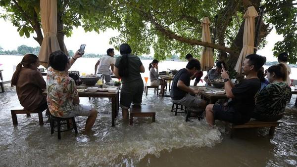 Namun badai tropi parah dan hujan monsun lebat menaikkan permukaan air sungai. Restoran pun tergenang.(Sakchai Lalit/AP)