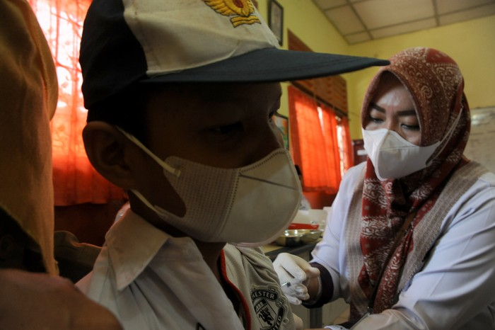 Petugas menyuntikkan vaksin COVID-19.pada salah satu pelajar SMP di Negeri 13 Palembang, Sumsel, Selasa (12/10/2021). Pemerintah Kota Palembang menargetkan sebanyak 192.671 pelajar di Kota Palembang untuk mendapatkan vaksin COVID-19. ANTARA FOTO/Feny Selly/hp.