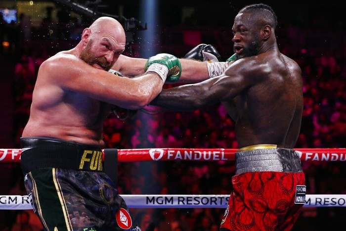 Tyson Fury, of England, left, fights Deontay Wilder in a heavyweight championship boxing match Saturday, Oct. 9, 2021, in Las Vegas. (AP Photo/Chase Stevens)