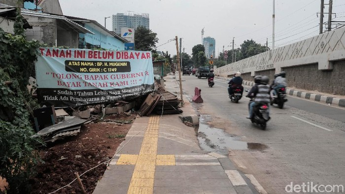 Sejumlah spanduk bertulisakan 'Tanah Ini Belum Dibayar' terpampang di sejumlah bidang tanah di dekat Flyover tapal kuda Tanjung Barat.