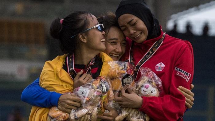 Atlet putri Bali Ni Made Eppi (kiri) bersama atlet putri Jawa Barat Ika Puspa Dewi (tengah) dan atlet putri DKI Jakarta Nadia Anggraini (kanan) berpelukan usai pengalungan medali Lompat Tinggi Putri PON Papua di Stadion Atletik Mimika Sport Centre, Kabupaten Mimika, Papua, Rabu (13/10/2021). Ni Made berhasil meraih medali emas, sementara atlet Jawa Barat Ika Puspa Dewi meraih medali perak dan atlet DKI Jakarta Nadia Anggraini meraih medali perunggu. ANTARA FOTO/Novrian Arbi/YU