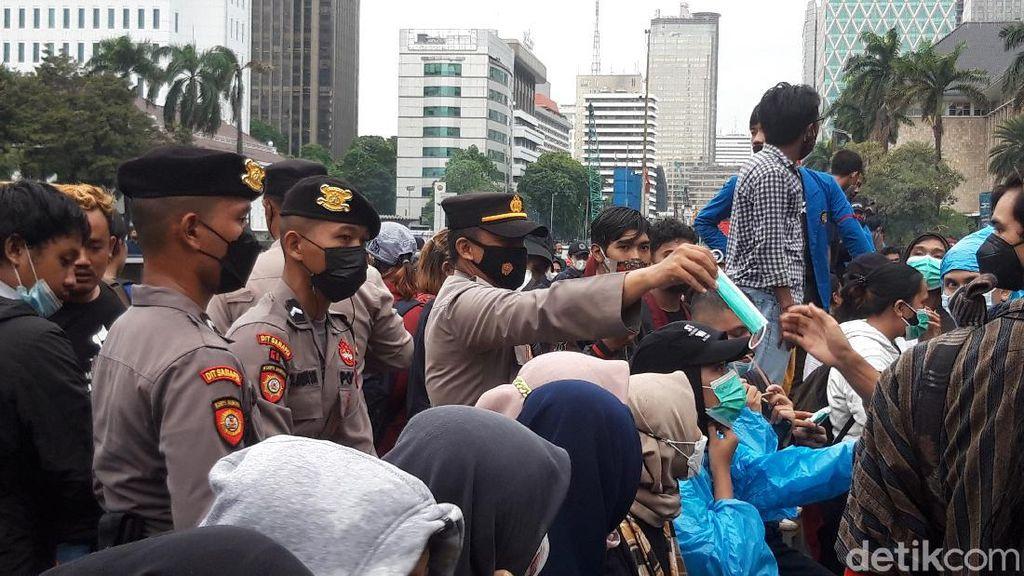 Polisi Bagi-bagi Masker ke Massa Demo di Patung Kuda: COVID Masih Ada!