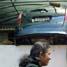 Sebuah mobil Toyota Avanza bernopol B 2304 IS berwarna hitam terangkat hingga ke atap garasi.
