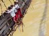 Tiga murid SD Negeri 02 Sangiangtanjung meniti jembatan miring saat menyebrangi Sungai Ciberang menuju rumah mereka, Selasa (17/1). Kurangnya perhatian Pemda terhadap insfrastruktur di desa ini membuat anak-anak ini bak menantang maut ketika pergi dan pulang sekolah. ANTARA/Asep Fathulrahman.
