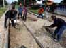 Beberapa pekerja mengeruk batu yang menutupi rel kereta api. Penutupan perlintasan kereta api liar tersebut untuk menghindari terjadinya insiden tertabraknya kendaraan oleh kereta.
