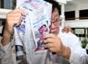 Kardius yang mengenakan kemeja warna putih menutupi wajahnya dengan koran.
