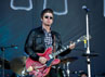 Noel tertangkap kamera beraksi dengan gitar elektrik merah dan gitar akustik. (Getty Images/Samir Hussein).