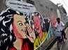 Seorang warga melintas di depan mural Pilkada di Jalan Daan Mogot, Jakarta.