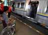Seorang penumpang menunggu kereta yang akan ditumpanginya di atas kursi roda.