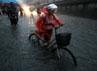 Seorang warga mendorong sepedanya melintasi jalanan yang tergenang banjir di Beijing. Reuters/China Daily.