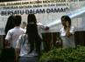 Siswa-siswi SMAN 70 membubuhkan tanda tangan di spanduk Mari Bersatu Dalam Damai yang dipasang di depan sekolah. Ramses/detikcom.